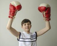 Muchacho en guantes de boxeo con las manos aumentadas en gesto de la victoria Fotos de archivo
