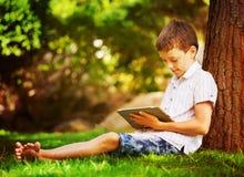 Muchacho en hierba con la tableta Foto de archivo libre de regalías