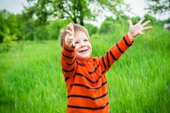 Muchacho en hierba verde con las manos aumentadas Imagen de archivo