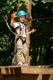 Muchacho en la actividad que sube en el cable de alta tensión Forest Park Imágenes de archivo libres de regalías