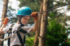 Muchacho en la actividad que sube en el cable de alta tensión Forest Park Foto de archivo