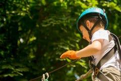 Muchacho en la actividad que sube en el cable de alta tensión Forest Park Fotos de archivo libres de regalías