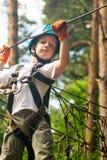 Muchacho en la actividad que sube en el cable de alta tensión Forest Park Fotografía de archivo