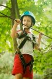 Muchacho en la actividad que sube en el cable de alta tensión Forest Park Fotografía de archivo libre de regalías