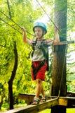 Muchacho en la actividad que sube en el cable de alta tensión Forest Park Imagenes de archivo