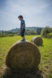 Muchacho en la bala de heno redonda Fotografía de archivo