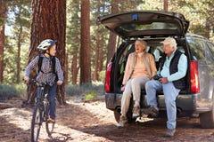 Muchacho en la bici y pares mayores en el coche que se prepara para un alza Foto de archivo libre de regalías