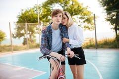 Muchacho en la bicicleta que mira soñador in camera mientras que muchacha hermosa con el pelo rubio que se coloca por otra parte  Fotografía de archivo libre de regalías