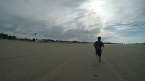 Muchacho en la camisa azul que corre en la arena metrajes