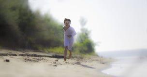 Muchacho en la camisa blanca, corriendo a lo largo de la orilla del río imagenes de archivo