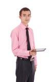 Muchacho en la camisa que sienta y que sostiene una tableta Foto de archivo