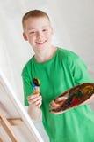 Muchacho en la camisa verde que sostiene la plataforma de los pintores Fotos de archivo libres de regalías