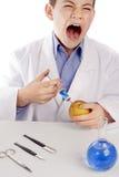 Muchacho en la capa del laboratorio que inyecta el líquido azul en manzana Imagenes de archivo
