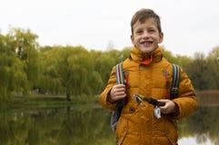 Muchacho en la chaqueta amarilla que celebra la caña de pescar al aire libre en la charca durante día fresco del otoño Fotos de archivo libres de regalías
