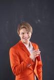 Muchacho en la chaqueta anaranjada con una taza de café Foto de archivo libre de regalías