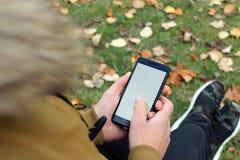 Muchacho en la chaqueta marrón que mira un smartphone fotos de archivo libres de regalías