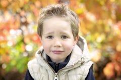 Muchacho en la estación del otoño en un parque Foto de archivo libre de regalías