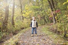 Muchacho en la estación del otoño en un parque Imágenes de archivo libres de regalías