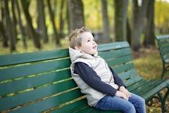 Muchacho en la estación del otoño en un parque Fotos de archivo