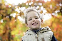 Muchacho en la estación del otoño en un parque Fotos de archivo libres de regalías