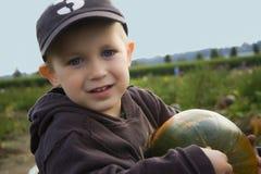Muchacho en la granja de la calabaza Foto de archivo libre de regalías