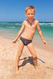 Muchacho en la playa con el mar en fondo Imagenes de archivo
