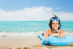 Muchacho en la playa con los matrass inflables en máscara del equipo de submarinismo Fotografía de archivo libre de regalías