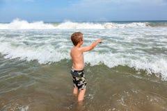 Muchacho en la playa que mira las ondas Foto de archivo
