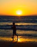 Muchacho en la puesta del sol en la playa en Mancora, Perú Imagen de archivo libre de regalías