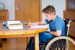 Muchacho en la silla de ruedas que hace la preparación Foto de archivo