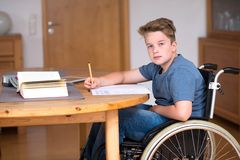 Muchacho en la silla de ruedas que hace la preparación Foto de archivo libre de regalías
