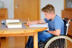 Muchacho en la silla de ruedas que hace la preparación Imagen de archivo