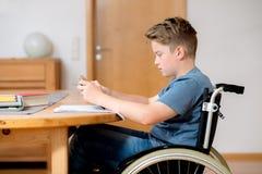 Muchacho en la silla de ruedas que hace la preparación y que usa la PC de la tableta Foto de archivo