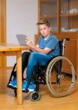 Muchacho en la silla de ruedas que hace la preparación y que usa la PC de la tableta Imagen de archivo libre de regalías