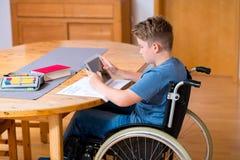 Muchacho en la silla de ruedas que hace la preparación y que usa la PC de la tableta Fotos de archivo