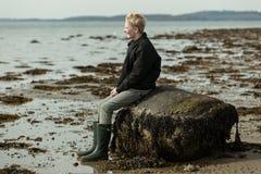 Muchacho en las botas que se sientan en roca vieja en la playa Imagenes de archivo
