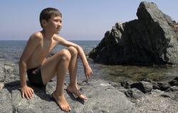 Muchacho en las vacaciones, sentándose en la roca Foto de archivo libre de regalías