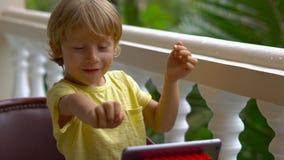 Muchacho en las zonas tropicales que habla con los amigos y la familia en la llamada video usando una tableta y los auriculares d metrajes
