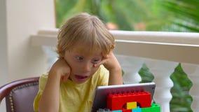Muchacho en las zonas tropicales que habla con los amigos y la familia en la llamada video usando una tableta y los auriculares d almacen de video