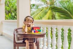 Muchacho en las zonas tropicales que habla con los amigos y la familia en la llamada video usando una tableta y los auriculares d Fotografía de archivo