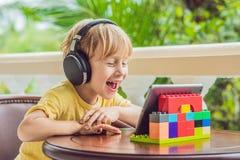 Muchacho en las zonas tropicales que habla con los amigos y la familia en la llamada video usando una tableta y los auriculares d Imagen de archivo