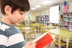 Muchacho en libro de lectura de la biblioteca fotografía de archivo libre de regalías