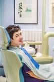 Muchacho en los apoyos de la demostración de la silla del dentista Imagen de archivo