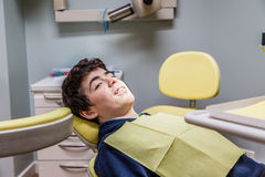 Muchacho en los apoyos de la demostración de la silla del dentista Imagen de archivo libre de regalías