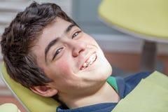 Muchacho en los apoyos de la demostración de la silla del dentista Fotos de archivo