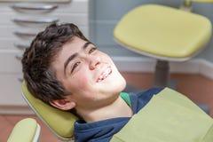Muchacho en los apoyos de la demostración de la silla del dentista Foto de archivo