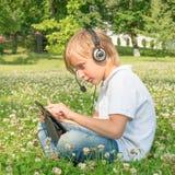 Muchacho en los auriculares que miran la tableta digital Foto de archivo