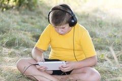 Muchacho en los auriculares que miran la tableta en Fotos de archivo libres de regalías