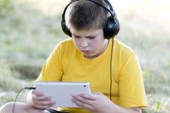 Muchacho en los auriculares que miran la tableta en Imagenes de archivo