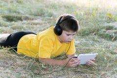 Muchacho en los auriculares que miran la tableta en Foto de archivo